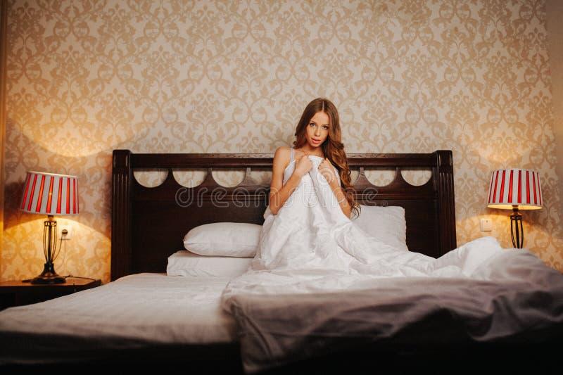 Naakte vrouw omvat door de deken op het bed stock afbeelding