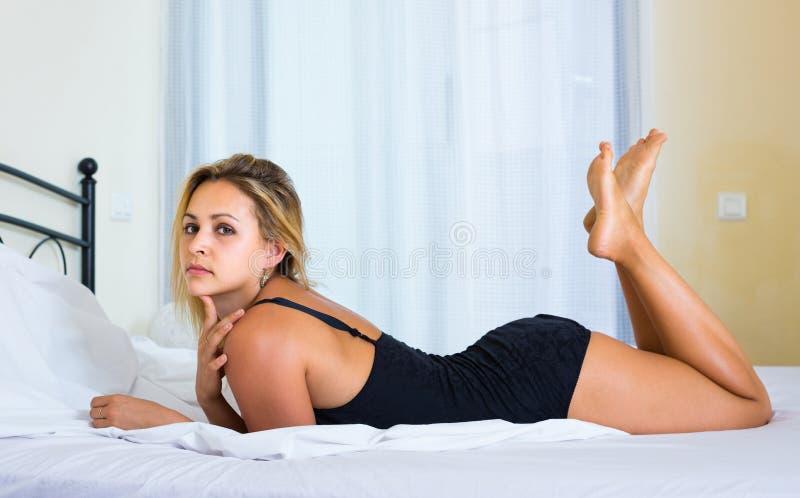 Naakte vrouw op bed in slaapkamer stock afbeelding