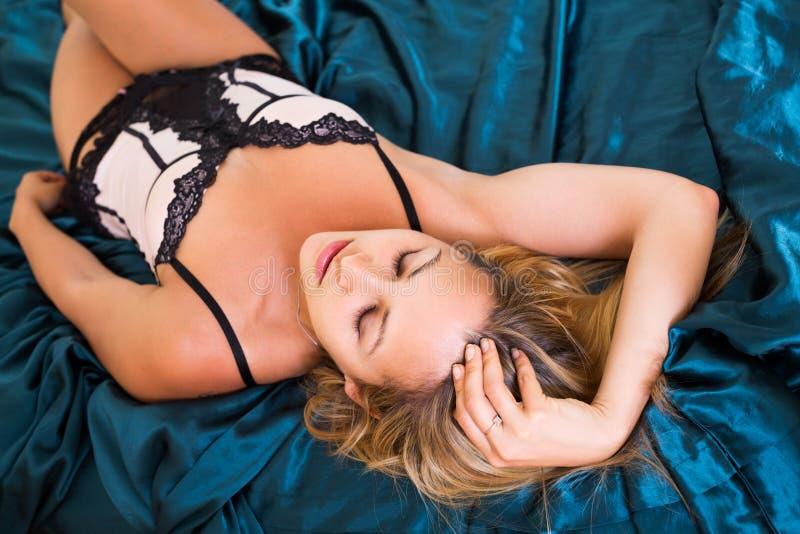 Naakte vrouw op bed in slaapkamer stock foto