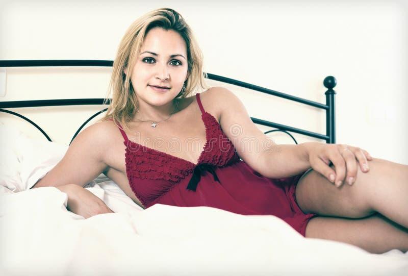 Naakte vrouw op bed in slaapkamer stock fotografie