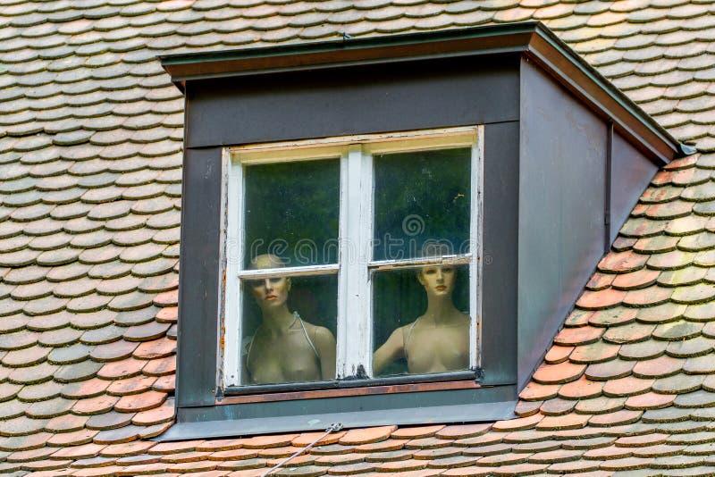 Naakte vrouwen achter een venster stock fotografie