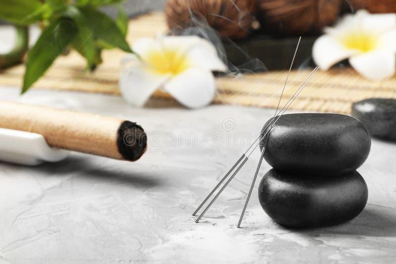 Naalden voor acupunctuur en stenen stock afbeeldingen