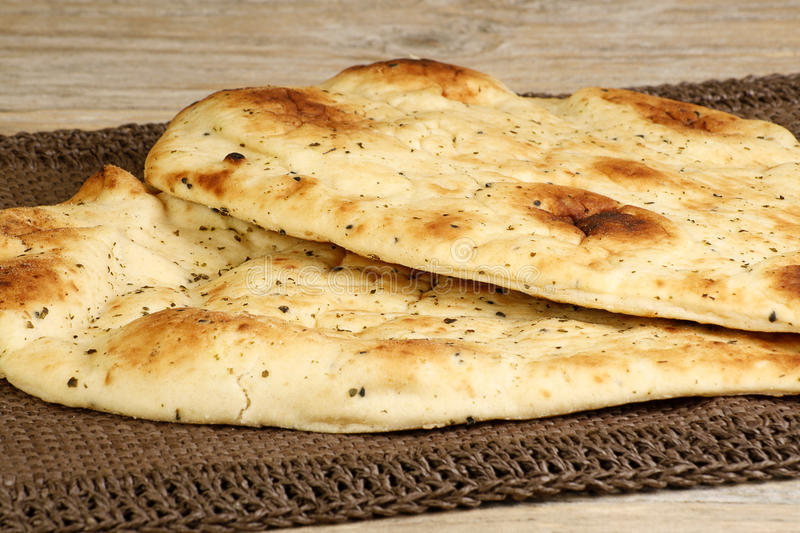 Naan bread. Two pieces of garlic and coriander naan on a wooden table royalty free stock photo