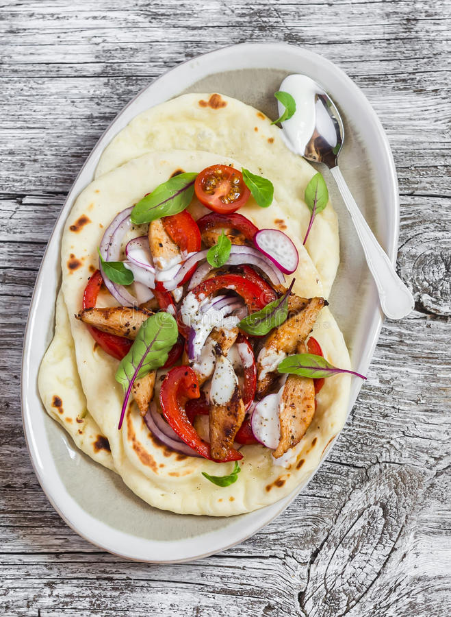 Naan bread with chicken vegetable stir fry and yogurt sauce on plate on rustic light wood background. Delicious food stock photo