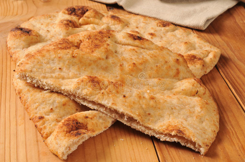 Naan bread. Sliced naan bread on a rustic wooden cutting board stock photo