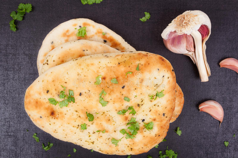 Naan bread, top view. Naan bread with fresh parsley herb and garlic on black background top view. Culinary indian and eastern cuisine stock photography