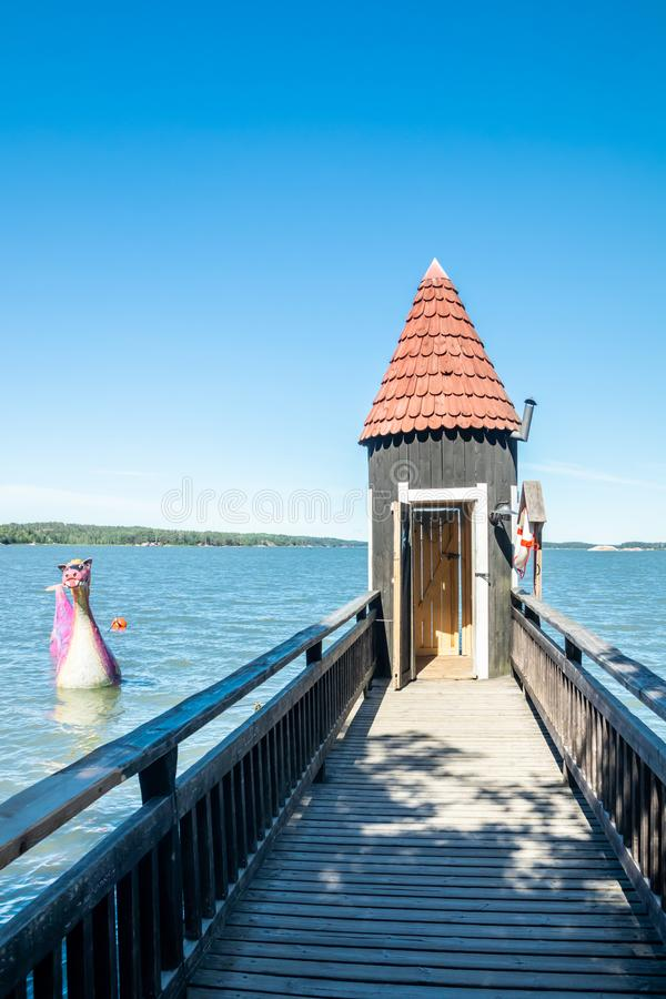 Naantali, Finland - 28 June, 2019: Bathing hut and Edvard the Booble in park Moominworld at sunny summer day royalty free stock photography