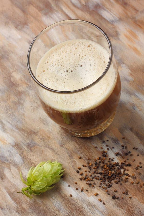 Naar huis gemaakt donker bier met zijn voorbereidingsingrediënten stock foto's