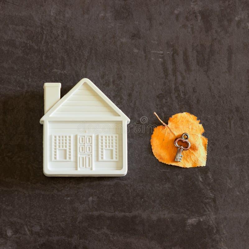 Naast een klein stuk speelgoed is het huis een sleutel op een geel de herfstblad stock foto