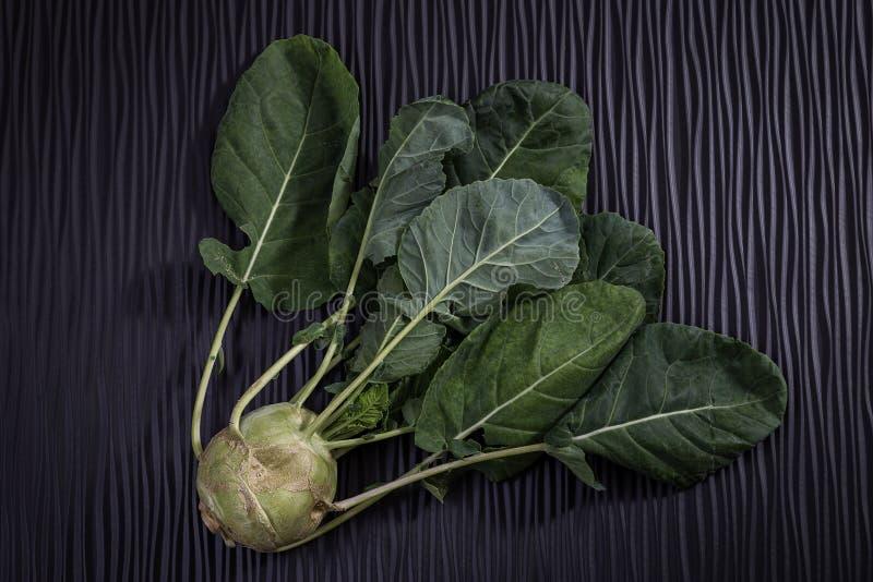 Nabo maduro con las hojas en un fondo negro de madera fotos de archivo