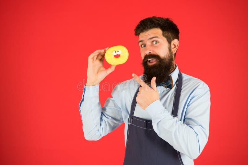 Nabranie posiłek Modnisia brodaty piekarniany chwyt glazurował pączek na czerwonym tle Kawiarnia i piekarni pojęcie Słodki pączek zdjęcie stock