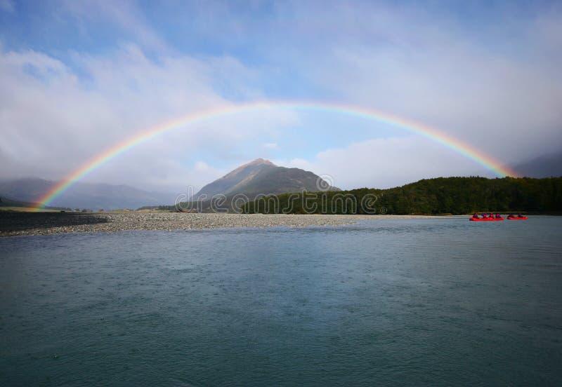 Nabrzeże z pełną tęczą na brzeg otokowej górze w pogodnym niebieskim niebie i kajakach w wodzie obraz stock