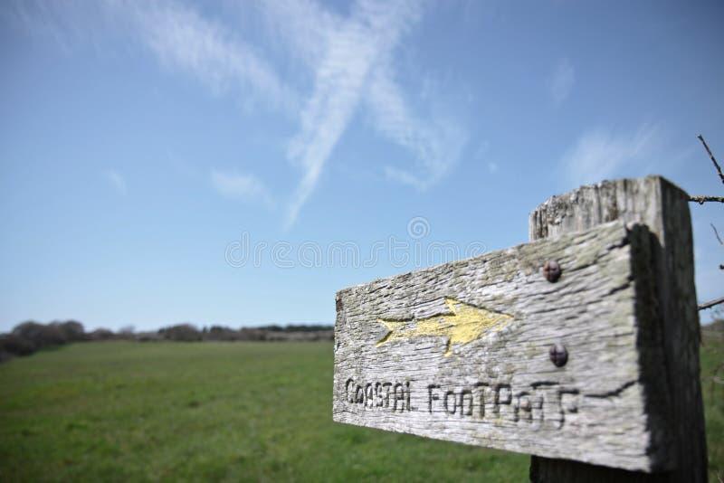 Nabrzeżnego footpath drewniana szyldowa poczta z strzała przeciw niebieskiemu niebu obrazy royalty free