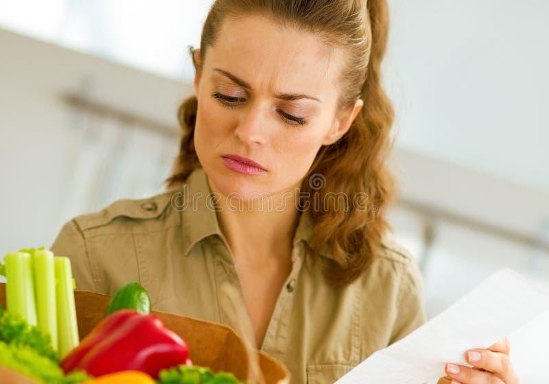 Nach dem Einkauf beteiligte junge Hausfrau überprüft Kontrolle stockbild