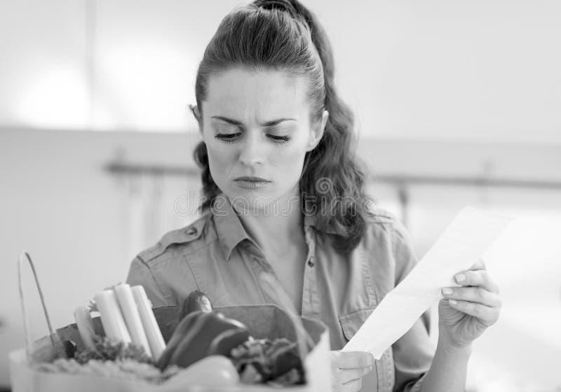 Nach dem Einkauf beteiligte junge Hausfrau überprüft Kontrolle stockbilder