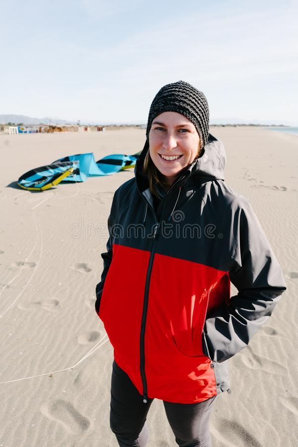 Nach dem Reiten des Drachens am kalten windigen Tag Frauenstellung auf dem Strand, lächelnd stockbilder