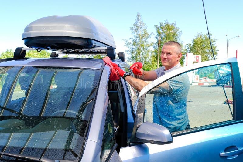 Nach dem Waschen des Autos der Mann wischt Windows trocken ab Autowashington-saubere Maschine, Autow?sche mit Schwamm und Schlauc stockbild