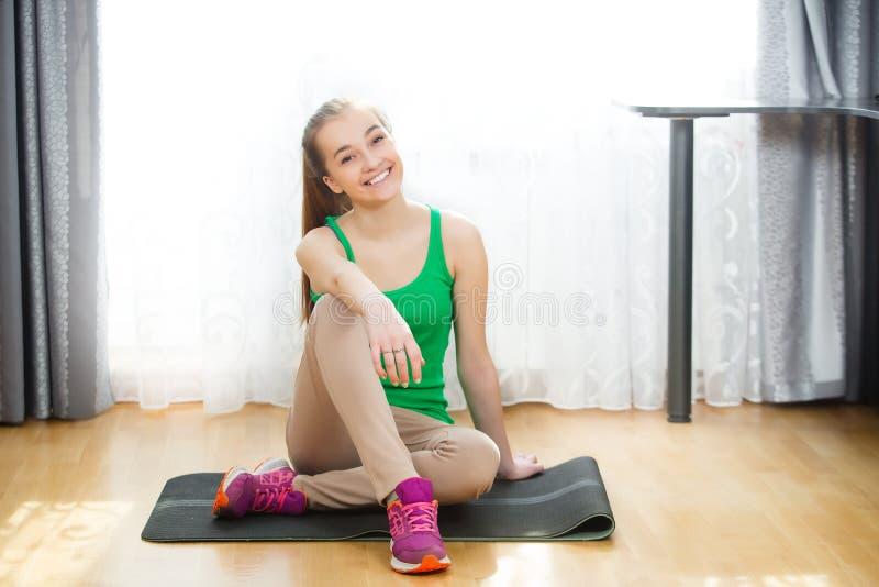 Nach der Ausbildung das schöne athletische Mädchensitzen entspannte sich auf Yogamatte lizenzfreies stockfoto