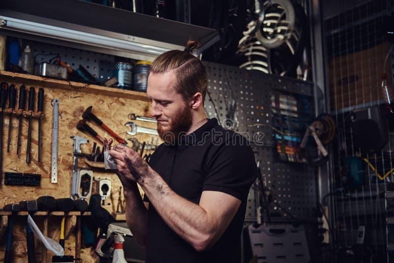Nach der Reparatur des Arbeitens in einer Werkstatt hübsche stilvolle Rothaarigearbeitskraft, seine schmutzigen Hände säubernd lizenzfreie stockbilder