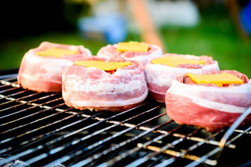 Nach Hause gemachte Bier-Dosen-Speck-Burger auf Grill machend, grillen Sie lizenzfreie stockfotos