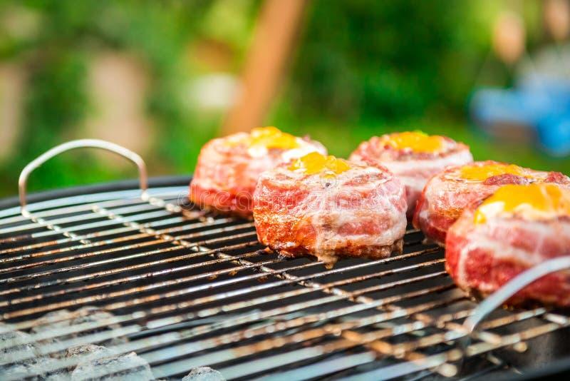 Nach Hause gemachte Bier-Dosen-Speck-Burger auf Grill machend, grillen Sie lizenzfreie stockbilder