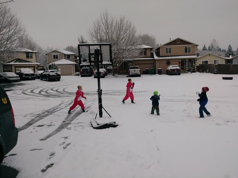 Nachbarschaftlicher Schneeballkampf unter Kindern stockfotografie