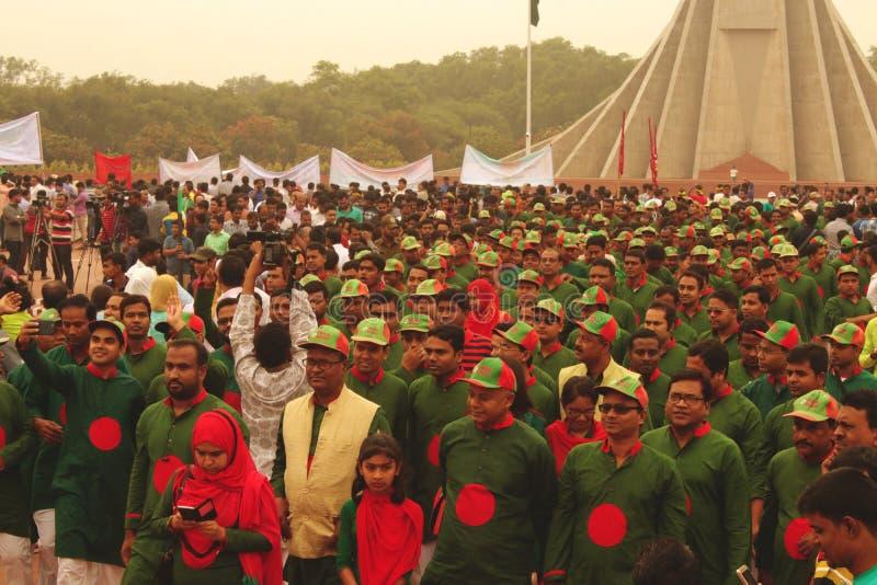 Nachdem sie Respekt zum nationalen Denkmal in Bangladesch gezahlt haben, gehen Leute zurück stockbild