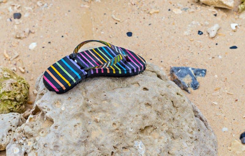 nachdem TsunamiFlipflops Sturm des sandigen Strandes verloren stockfotos