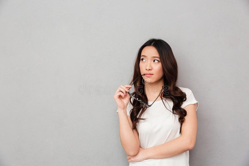 Nachdenkliche asiatische Frau im T-Shirt, das Brillen hält und weg schaut lizenzfreie stockbilder