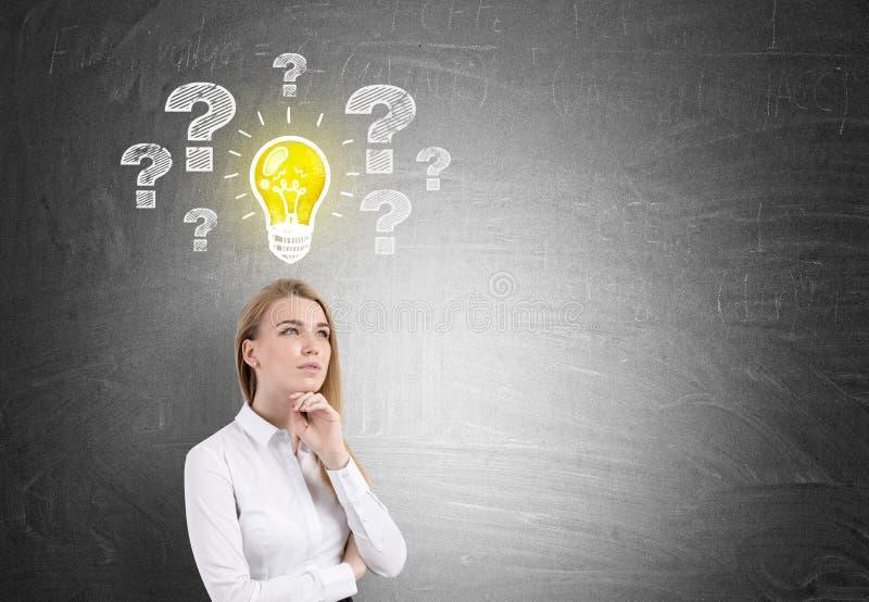Nachdenkliche blonde Frau, Glühlampe und Fragen lizenzfreie stockfotos