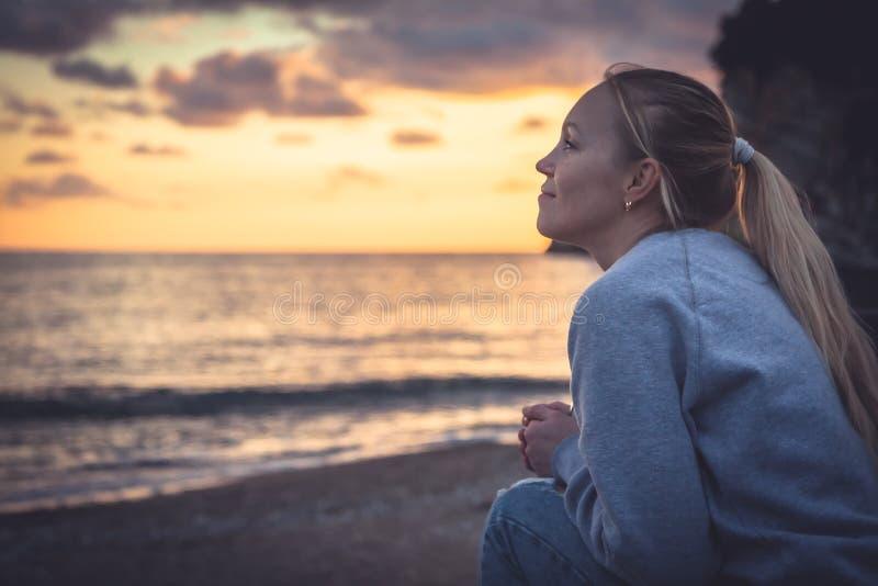 Nachdenkliche einsame lächelnde Frau, die mit Hoffnung in Horizont während des Sonnenuntergangs Strand betrachtet stockbild