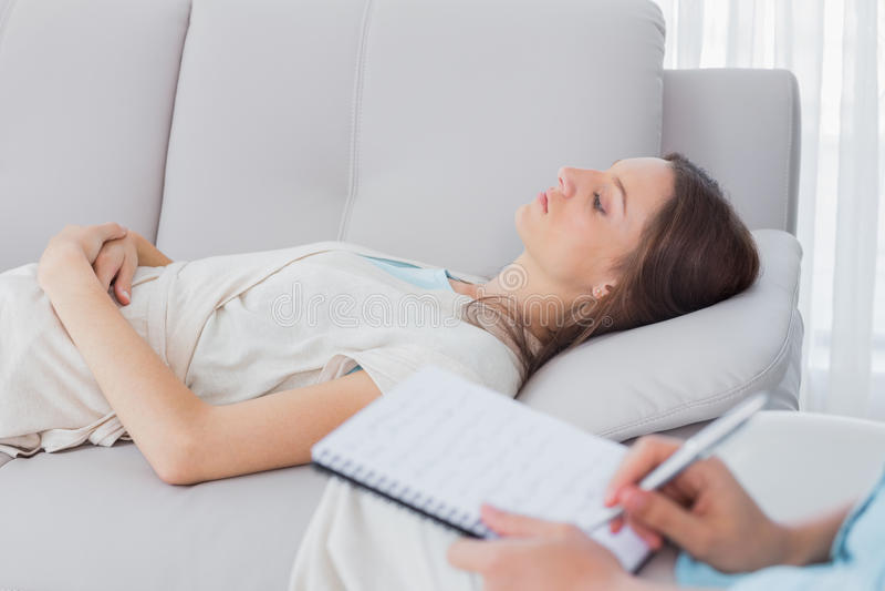 Nachdenkliche Frau, die auf der Couch während Psychologeschreiben liegt stockbilder
