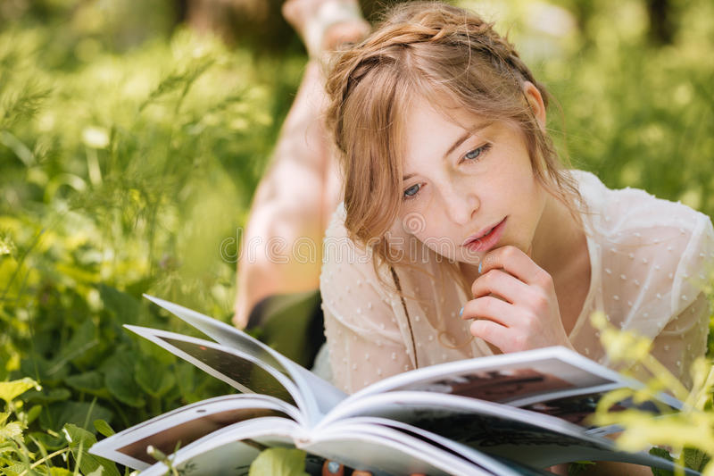 Nachdenkliche Frau, die auf Gras liegt und Zeitschrift liest stockbild
