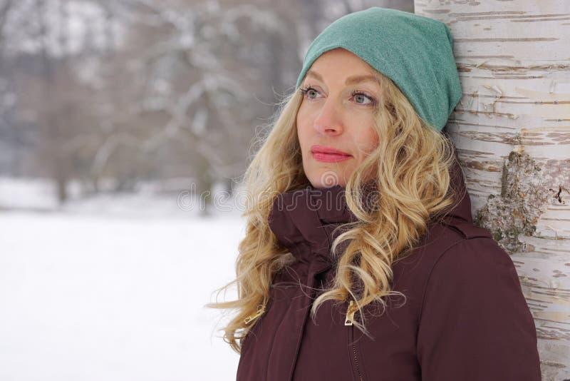 Nachdenkliche Frau, die am Baum im Winter sich lehnt stockfoto