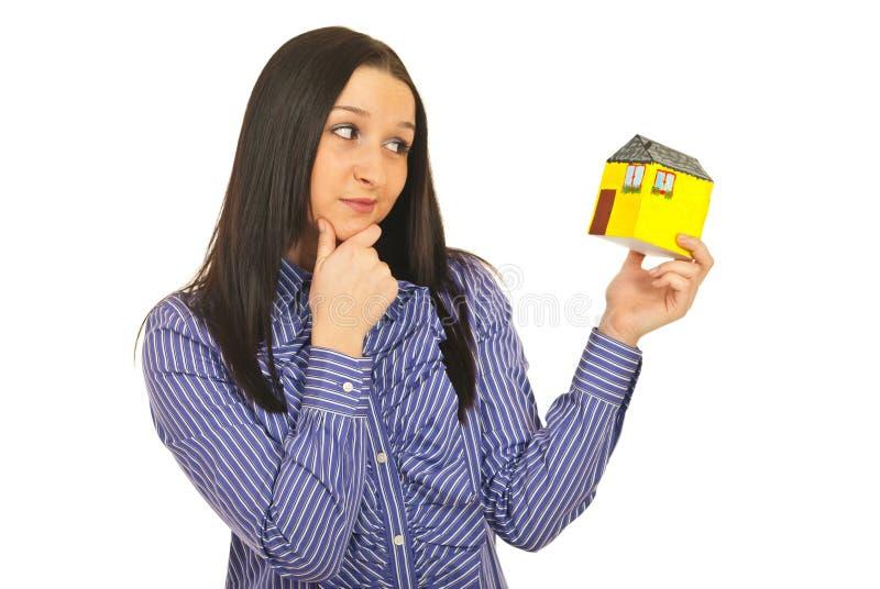 Nachdenkliche Frau, die Minihaus anhält lizenzfreies stockfoto