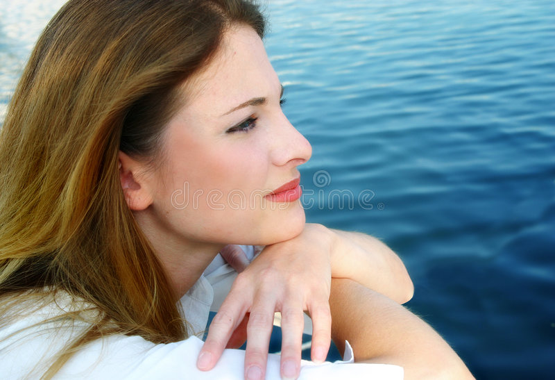 Nachdenkliche Frau durch Water stockfoto