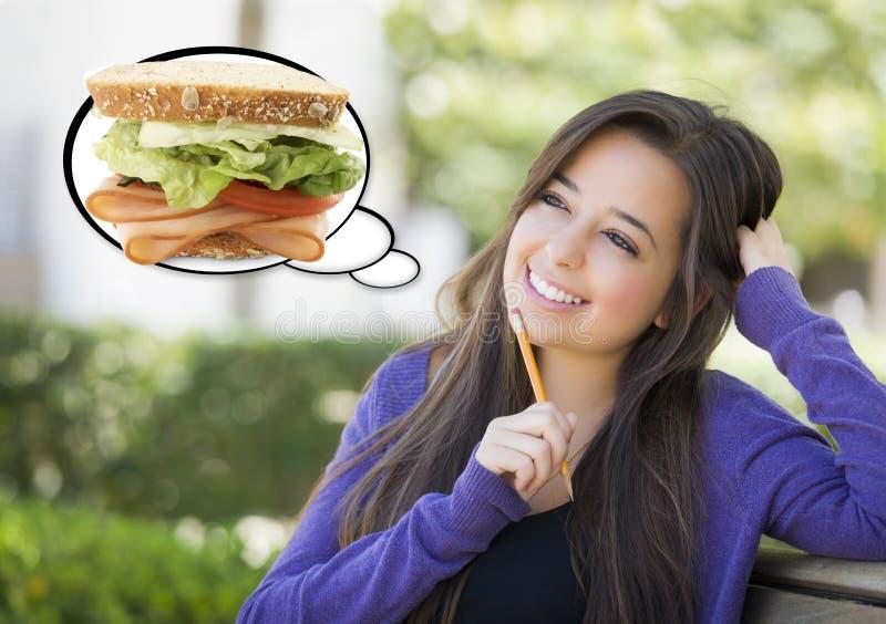 Nachdenkliche Frau mit großem Sandwich innerhalb der Gedanken-Blase stockbild