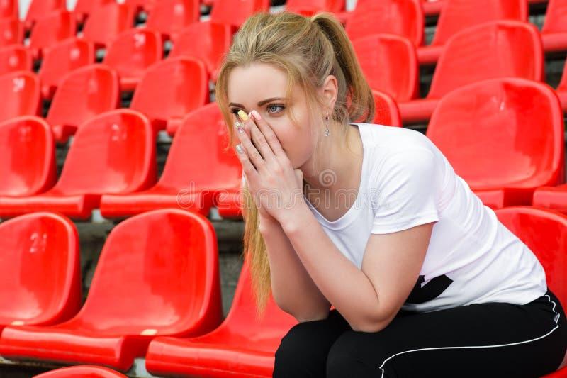 Nachdenkliche Frauencheerleader, die auf dem Stadionspodiumlehnsessel sitzt stockfoto