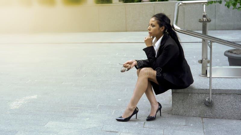 Nachdenkliche Geschäftsdame, die herein im Stadtzentrum gelegenes, stressiges Leben in der Großstadt, Karriere sitzt stockfotos