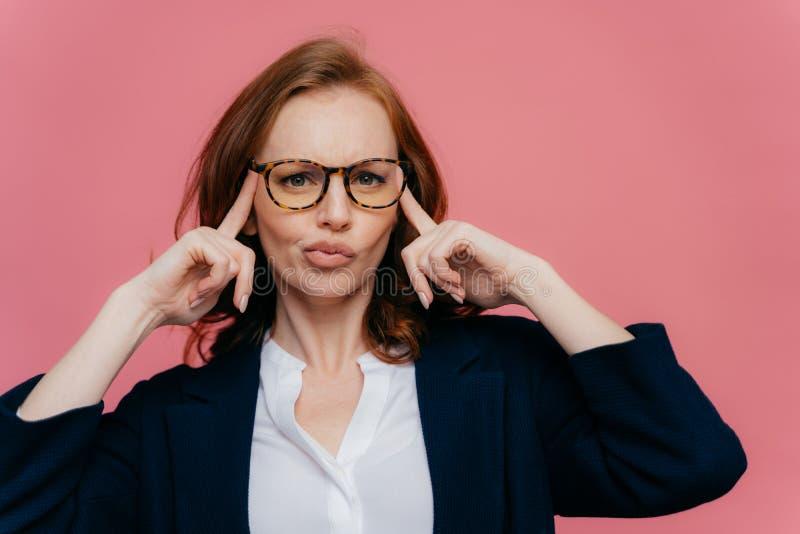 Nachdenkliche Geschäftsfrau berührt Tempel, versucht, mit Gedanken zu erfassen, betrachtet verwirrend Kamera, hat rotes Haar, trä stockfoto