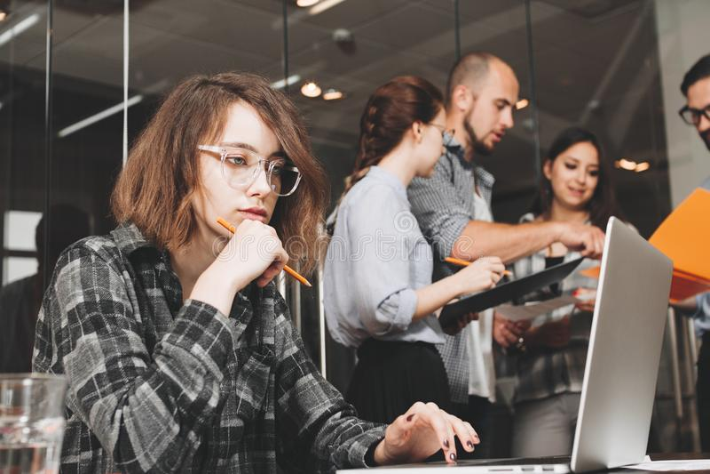Nachdenkliche Geschäftsfrau, die herein zusammen mit Teamkollegen arbeitet lizenzfreies stockfoto