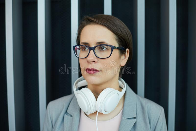 Nachdenkliche Geschäftsfrau mit Kopfhörern auf Hals lizenzfreie stockbilder