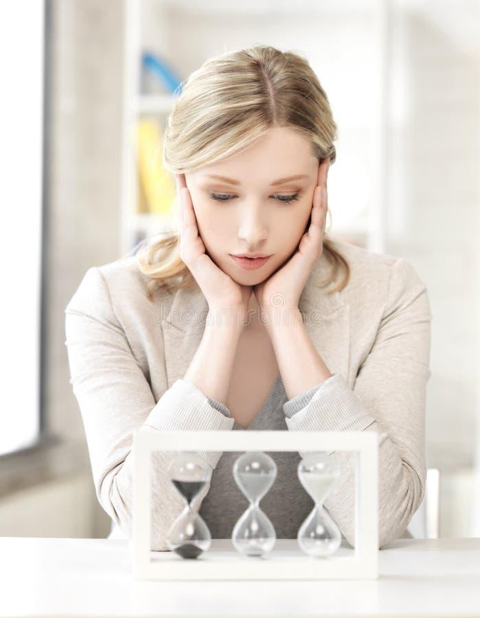 Nachdenkliche Geschäftsfrau mit Sandglas lizenzfreie stockfotografie