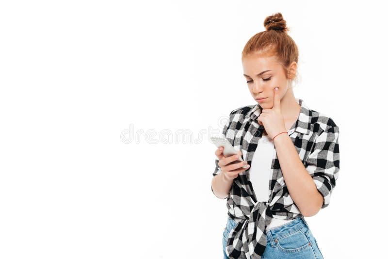 Nachdenkliche Ingwerfrau im Hemd und in den Jeans unter Verwendung des Smartphone stockfotografie