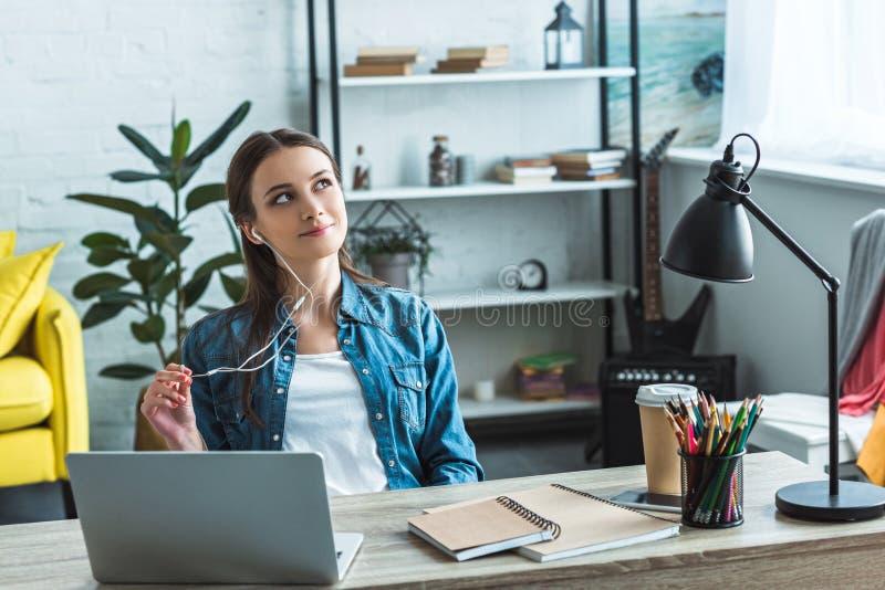 nachdenkliche Jugendliche in den Kopfhörern, die bei Tisch sitzen und weg beim Studieren mit Laptop schauen lizenzfreie stockfotografie