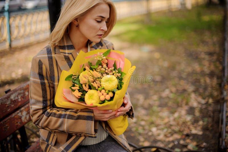Nachdenkliche junge Blondine im Plaidmantel, der auf Bank mit einem Blumenstrauß von gelben Blumen sitzt lizenzfreies stockbild