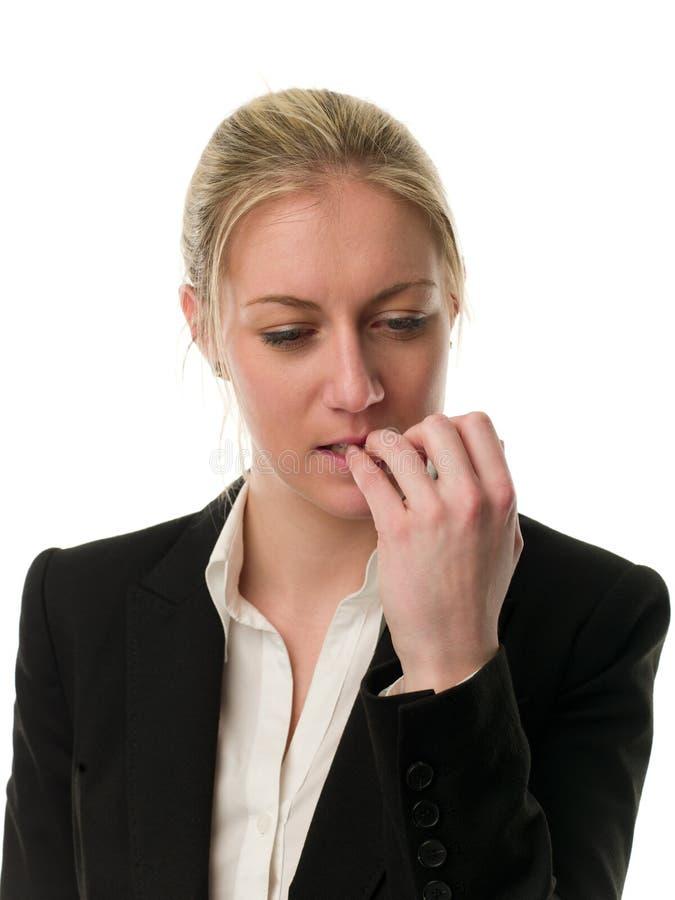 Nachdenkliche junge Geschäftsfrau, die ihre Nägel beißt stockfotografie