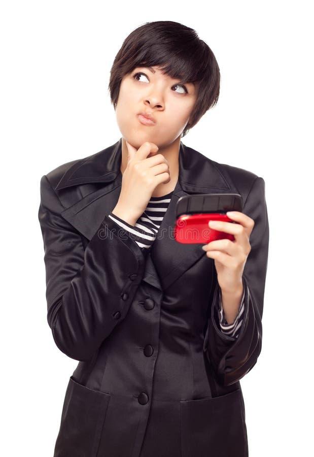 Nachdenkliche junge Mischrasse-Frau mit Handy auf Weiß stockfotografie