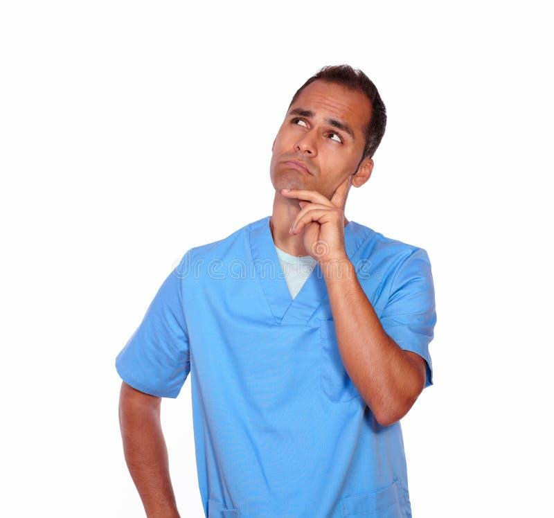 Nachdenkliche männliche Krankenschwester, die mit der Hand auf Kinn steht stockfotografie