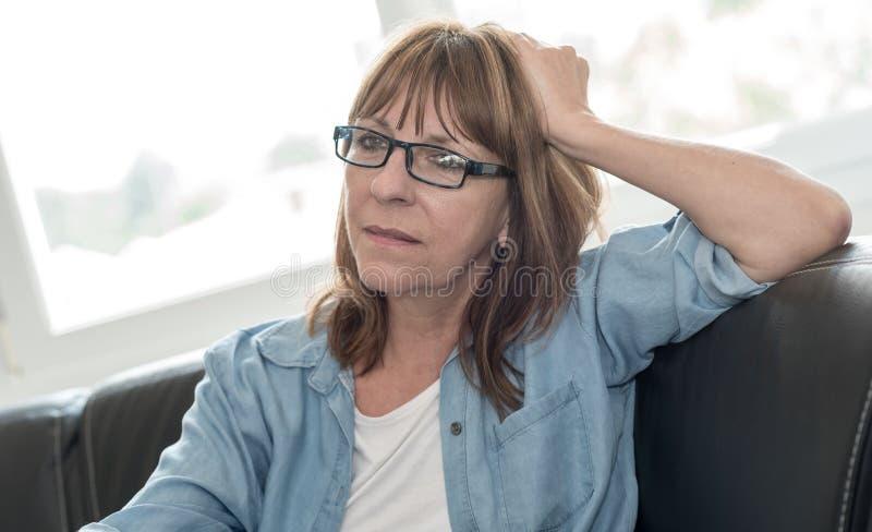 Nachdenkliche reife Frau, die auf Sofa sitzt lizenzfreie stockfotos